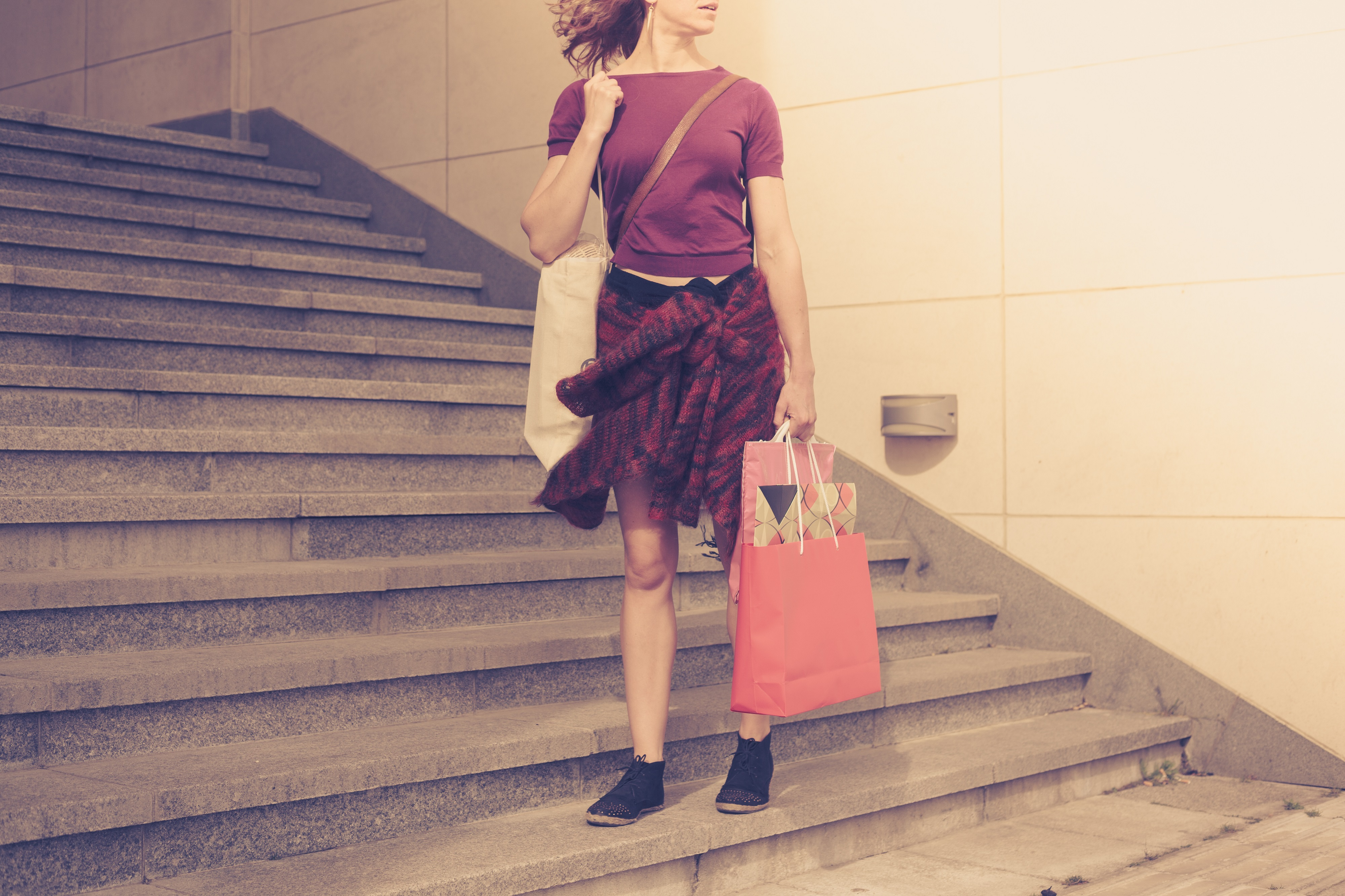 A young woman with shopping bags is standing by some stairs outside at sunset