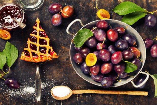 overhead view of fresh plum pie or tart and plums on dark rustic background