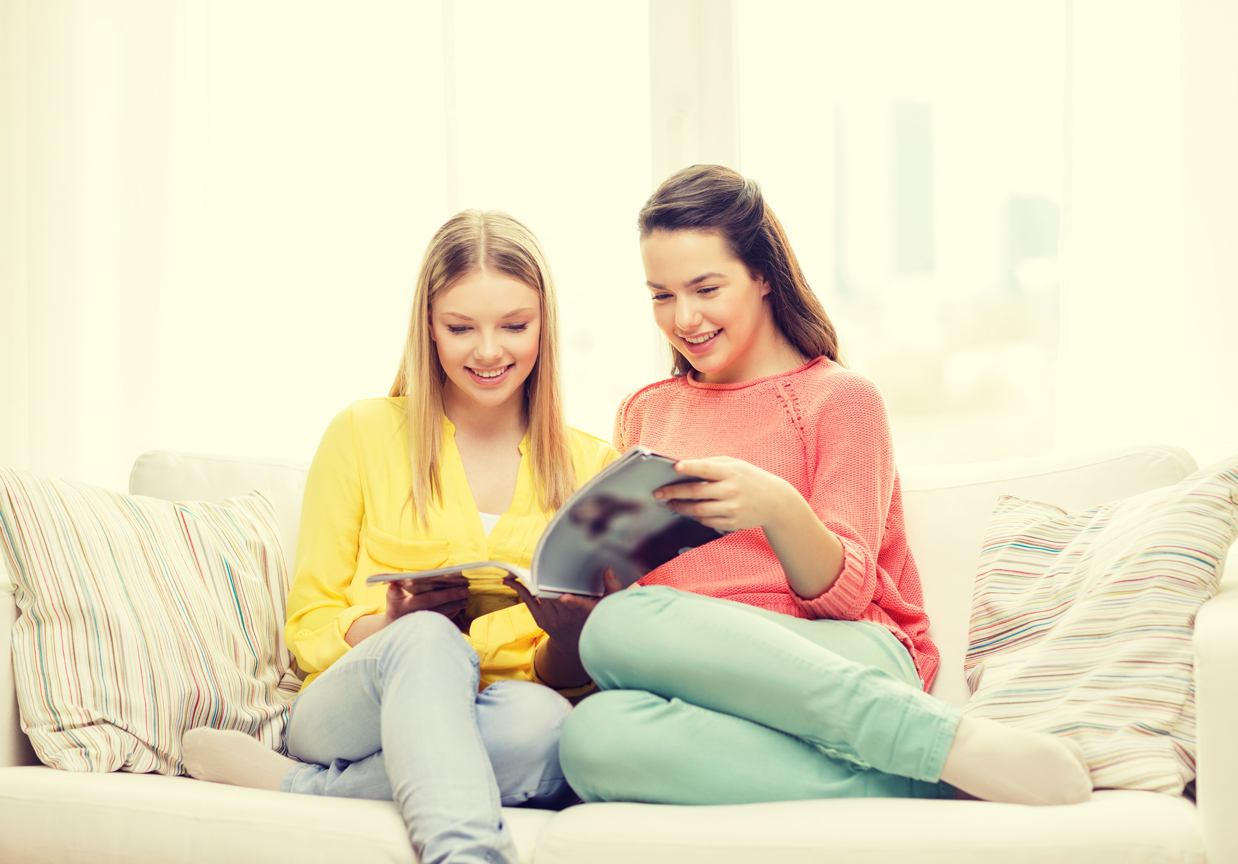 friendship and happiness concept - two girlfriends reading magazine at home