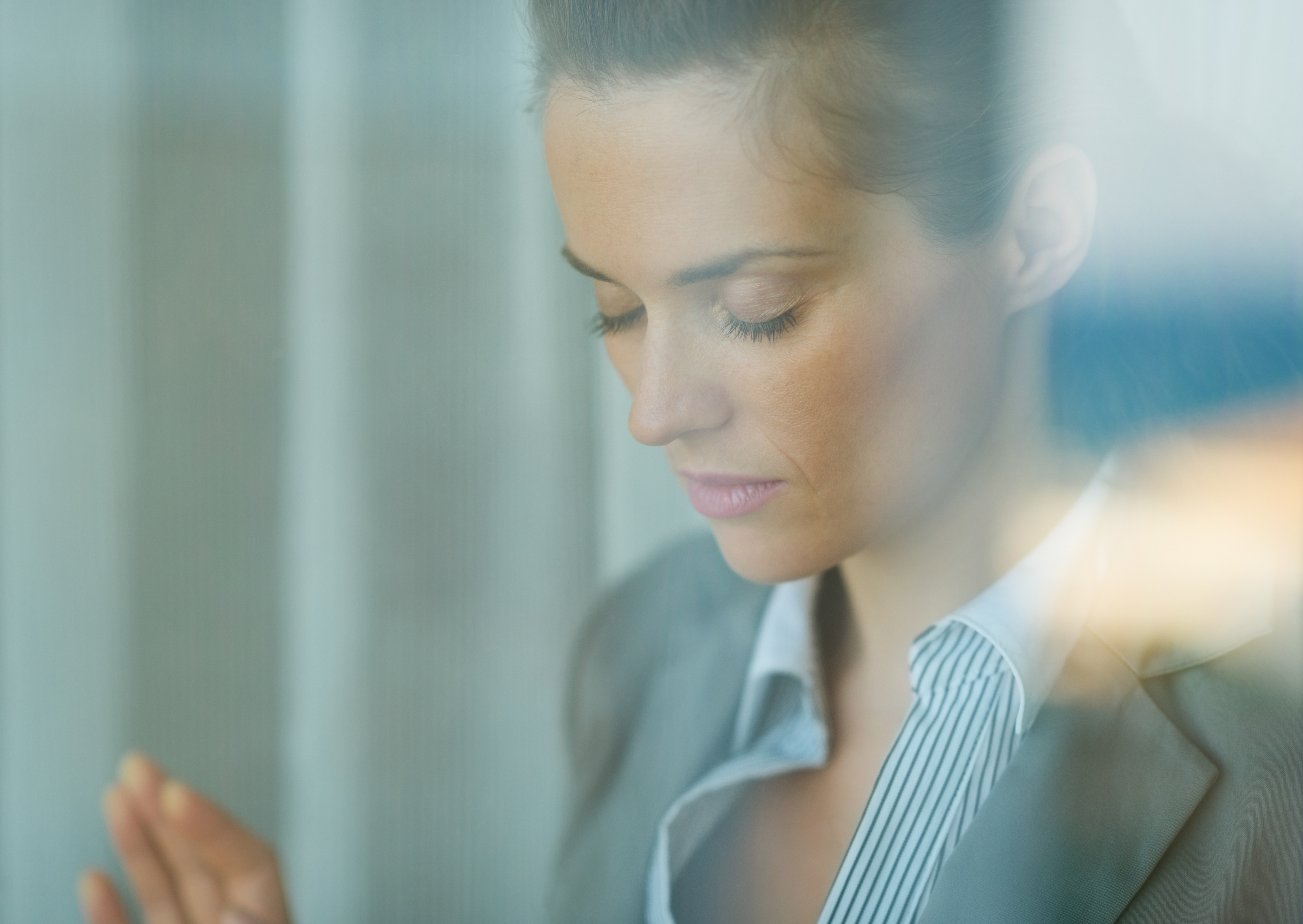 Portrait of thoughtful business woman leaning on window
