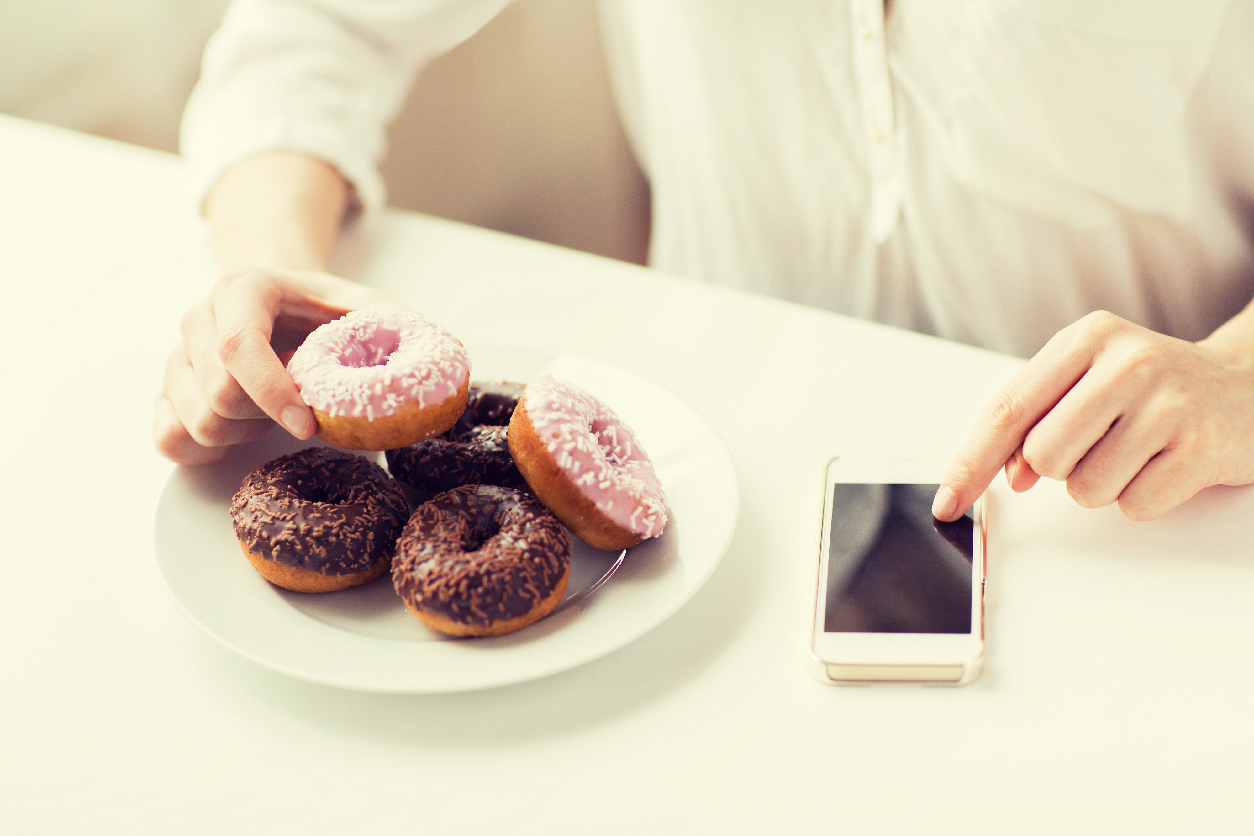 people, junk food, diet, technology and unhealthy eating concept - close up of hands with smart phone and donuts counting calories and sitting at table at home