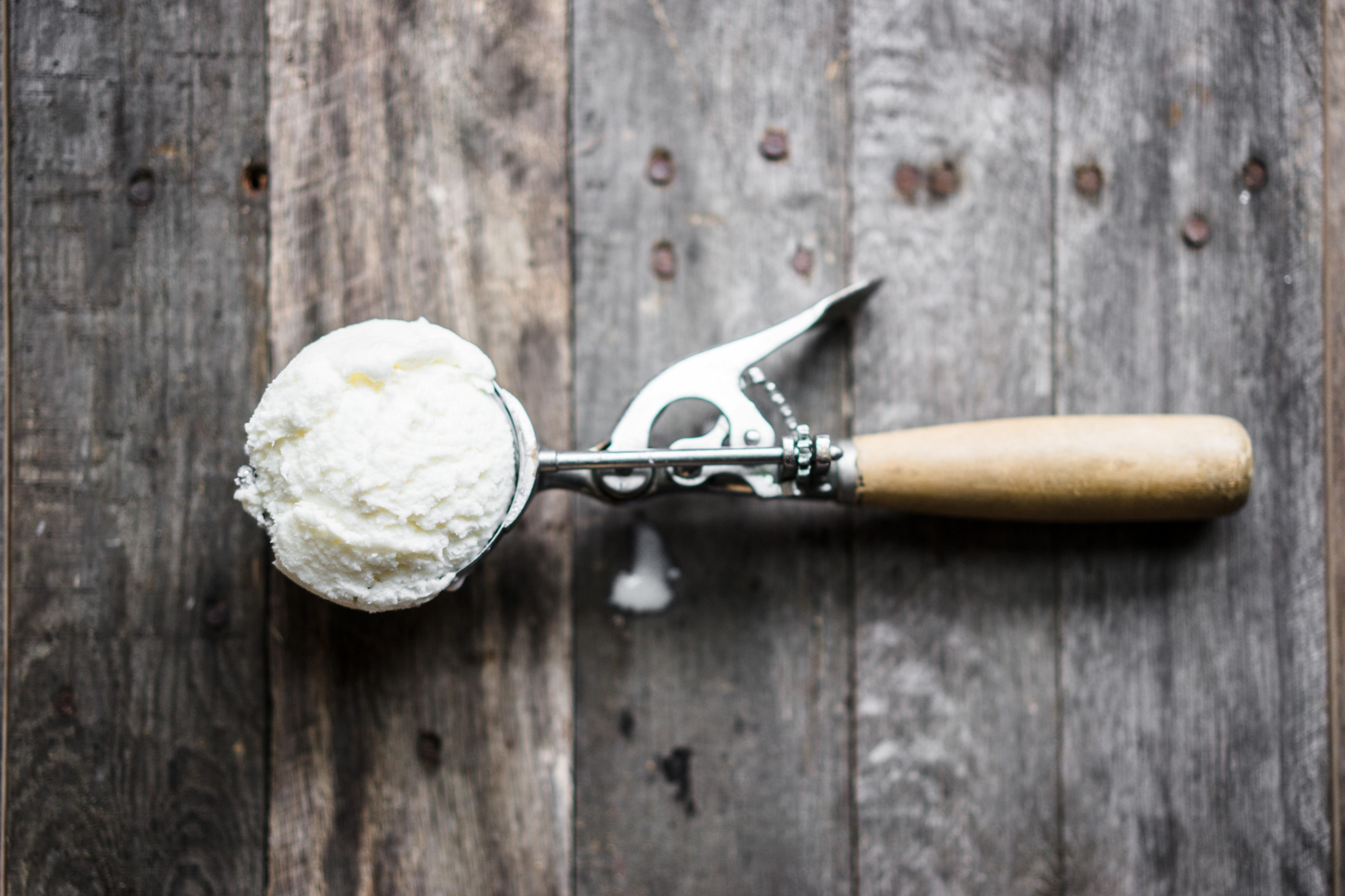Scoop of vanilla ice-cream on rustic wooden background