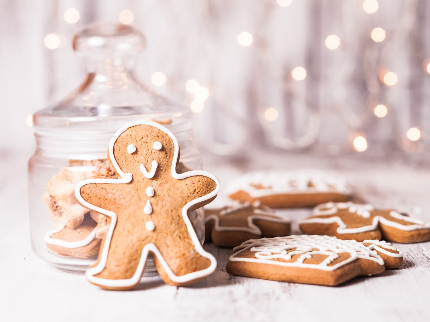 Gingerbread cookies on a table and Christmas lights on background