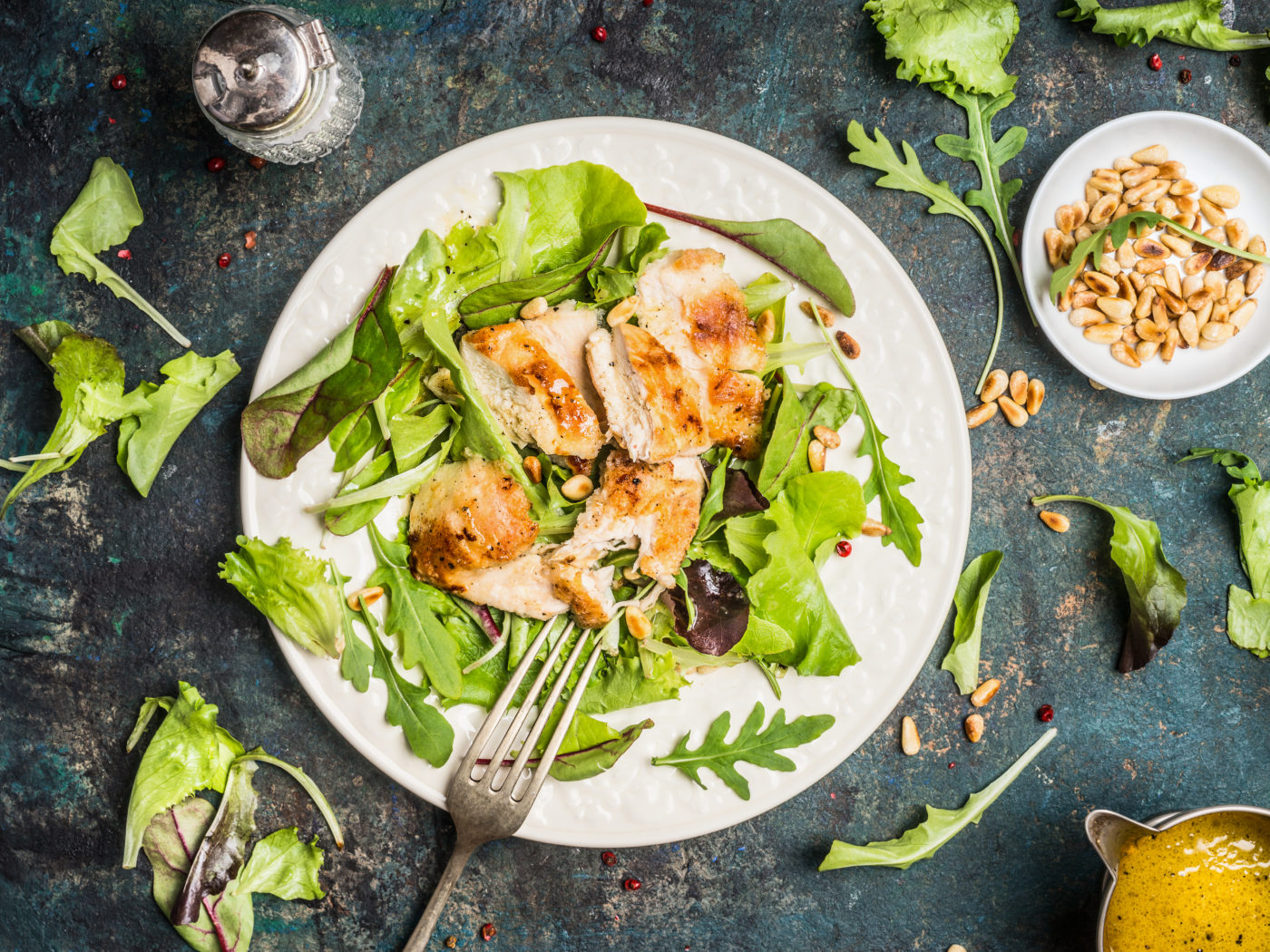 Chicken green salad served on rustic table with pine nuts and oil dressing, top view