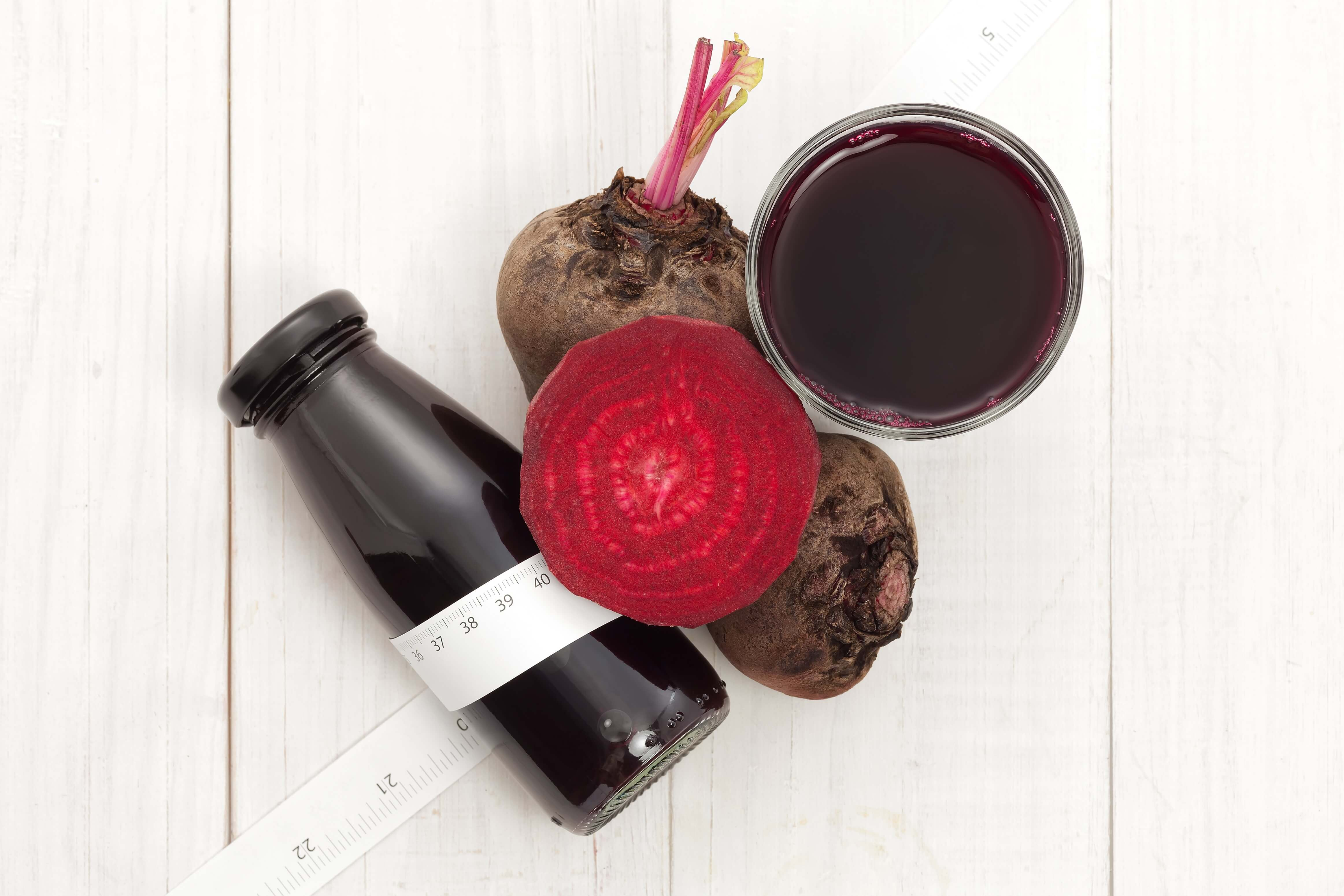 Beetroot with beet juice and mesuring tape