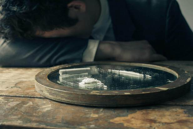 Young businessman is feeling unwell after doing cocaine