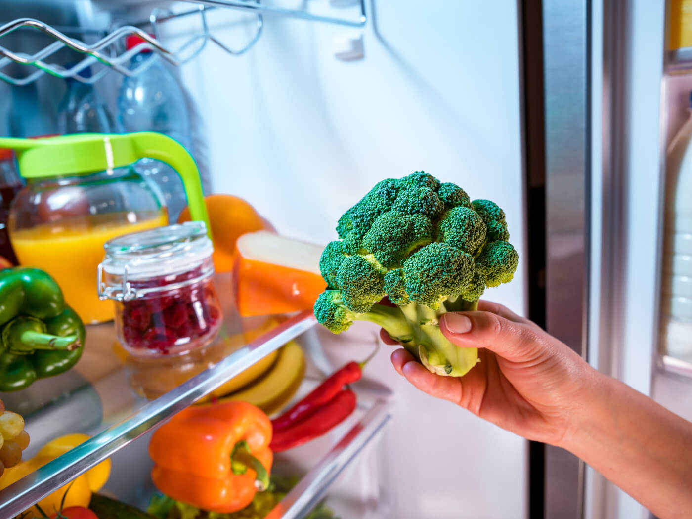Woman takes the broccoli from the open refrigerator. Healthy food.