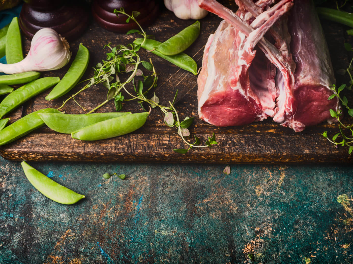 Rack of lamb with green pea pods, cooking preparation on rustic background, top view, border