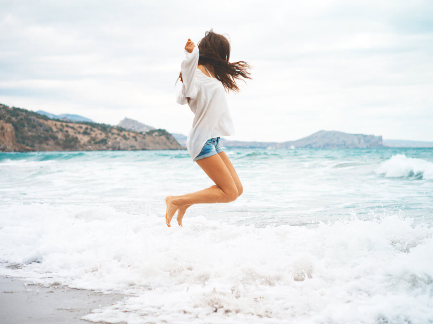 Outdoor photo of beautiful young woman jumping at the sea