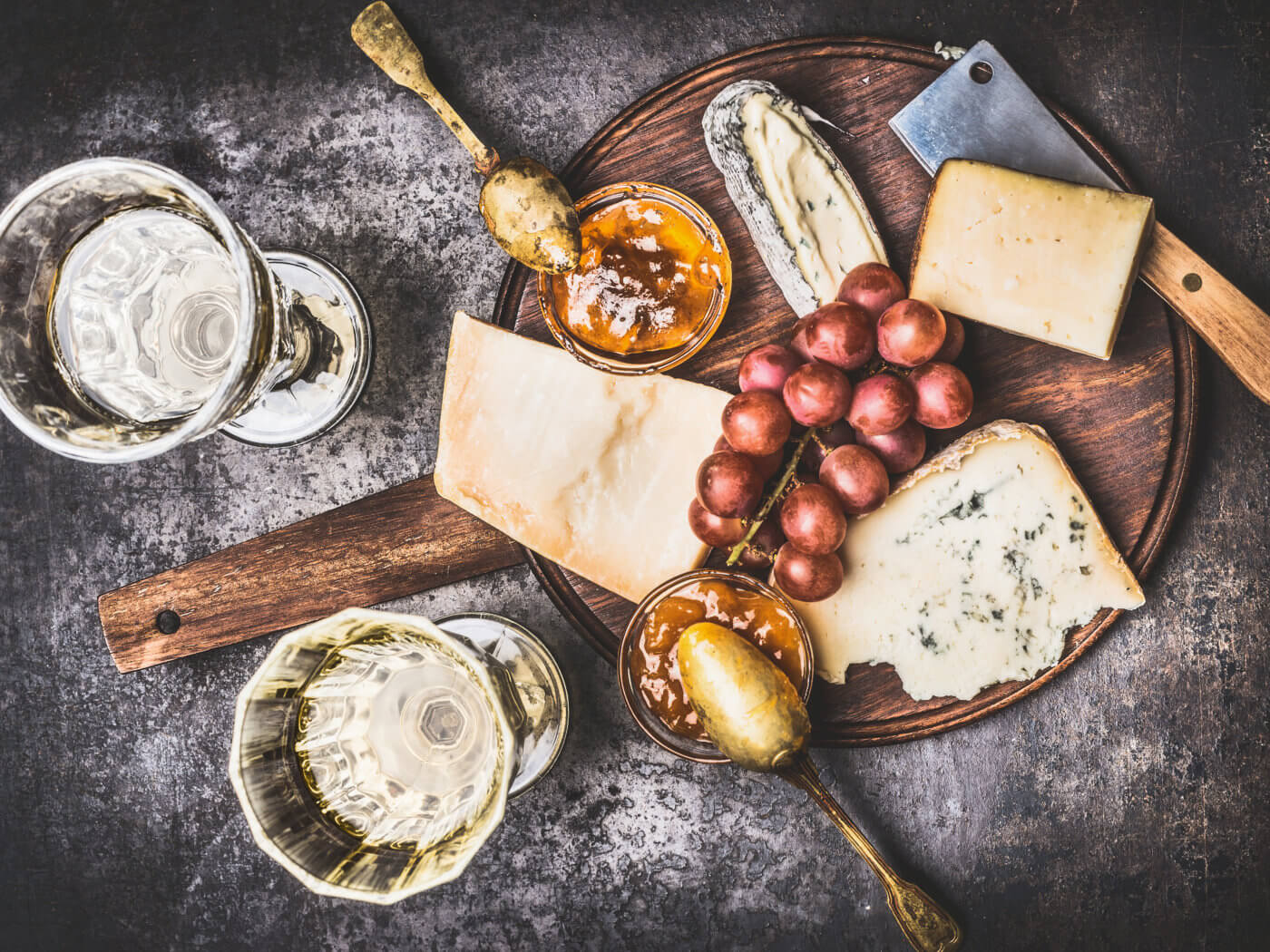 Appetizing fine cheese selection on rustic plate with wine, grape and Honey mustard sauce , top view