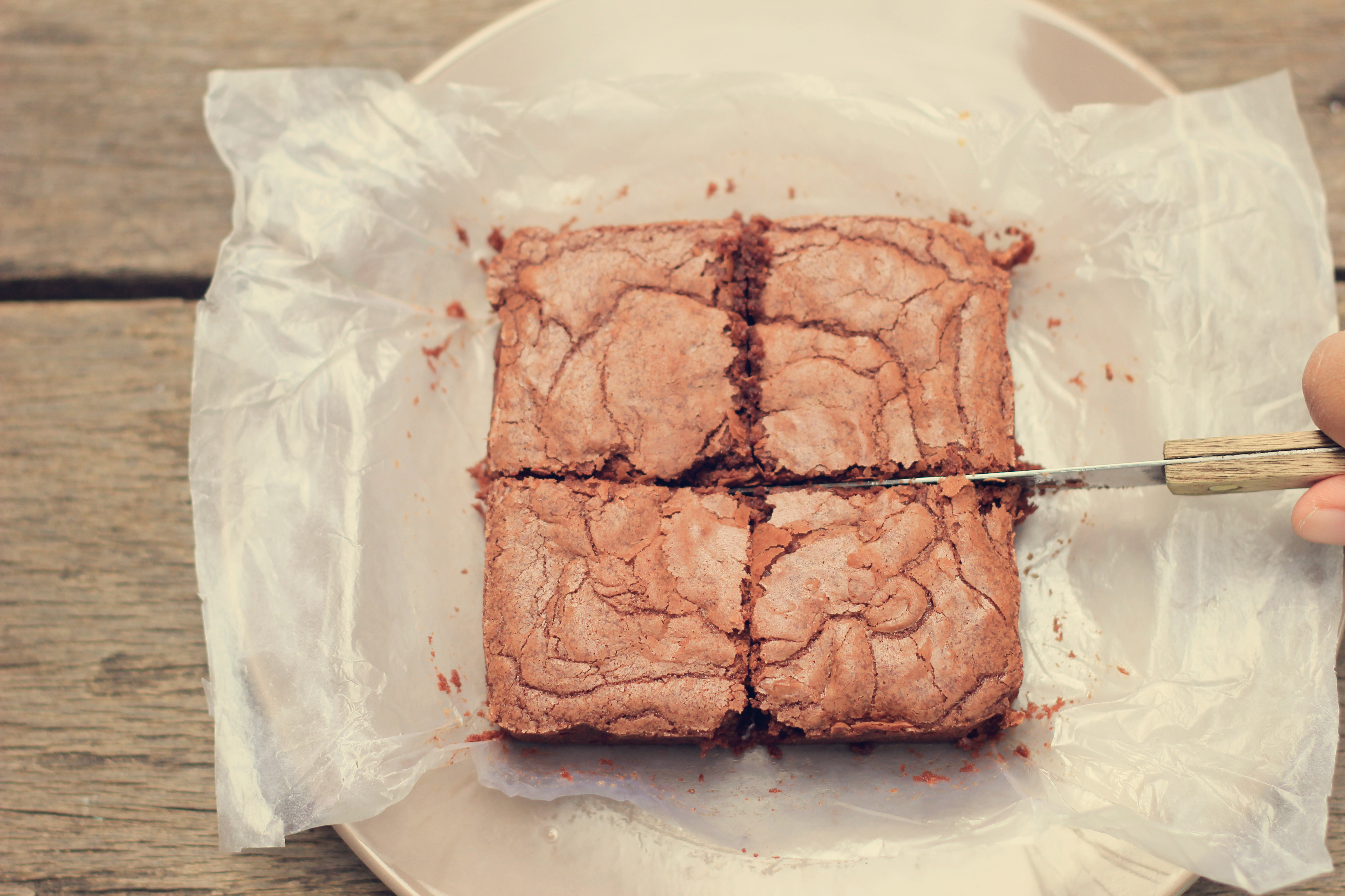 Cutting crispy homemade brownie with retro filter effect